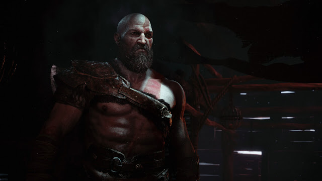 The character Kratos stands sullen in a wooden shack, from God of War
