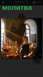 В помещении церкви около подставки для свечей стоит молится женщина в платке в свете солнечных лучей