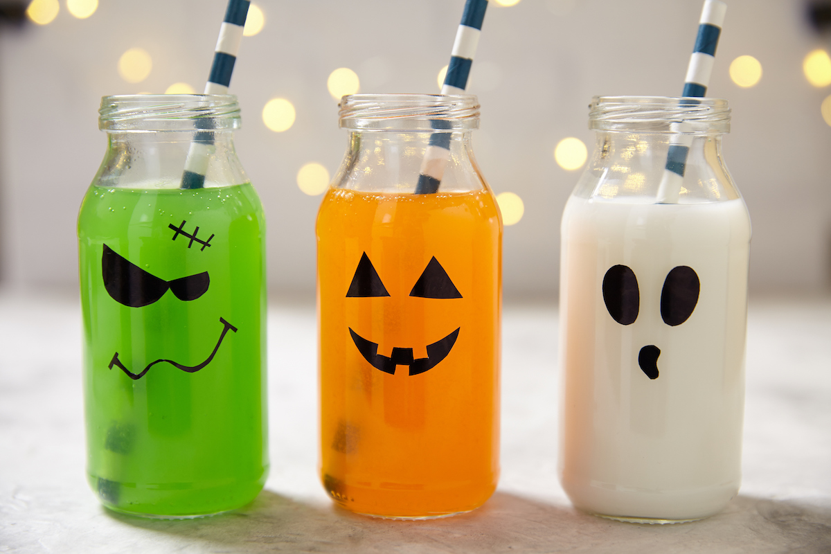 botellas con caras pintadas para servir bebida en halloween