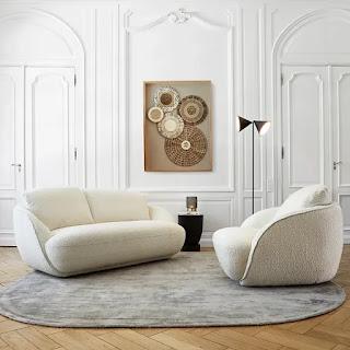canapé et fauteuil blancs en laine bouclée dans un intérieur haussmanien sur tapis rond en tons neutres