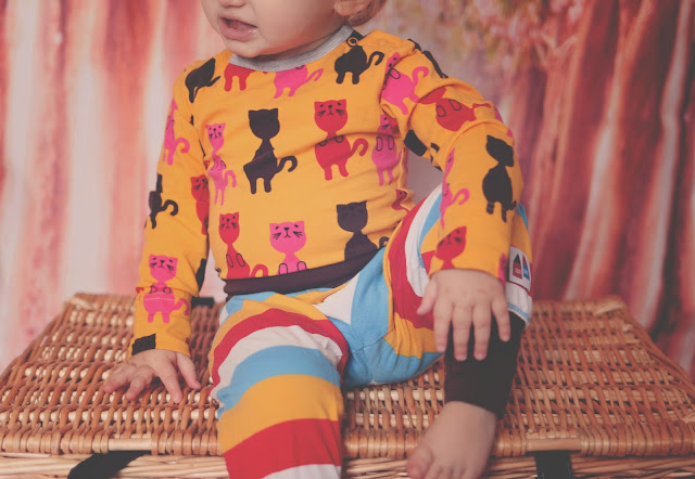 toddler girl wearing colourful clothing from me&i mustard, brown, pink and red kitten body suit and mustard, blue, white, red and brown first striped pants