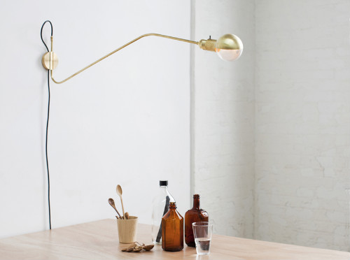 Mit ihrem langen Arm kommt die Wandlampe aus Messing über einem schlichten Esstisch schön zur Geltung