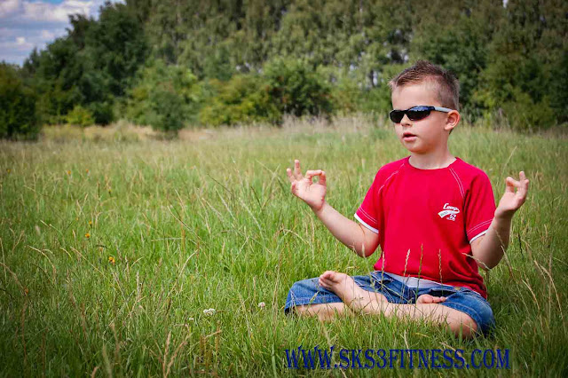 A kid meditating in Lotus Pose with Gyan Mudra / hand gesture on grass in Sunny days of summer