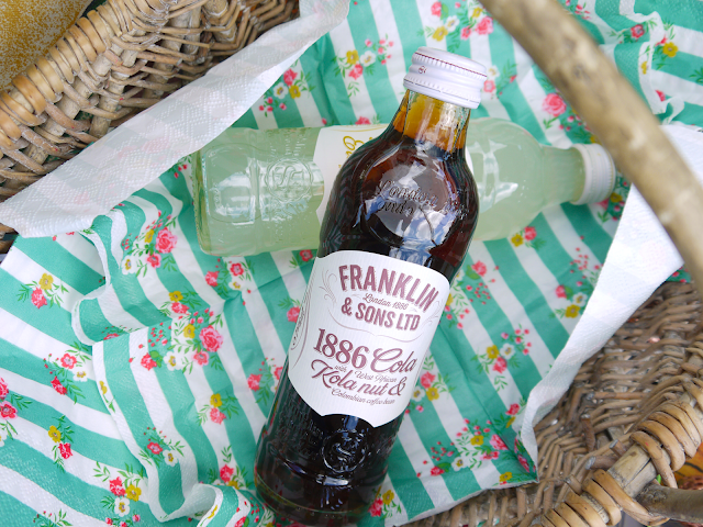 franklin and sons glass bottles lay on green napkins in a wicker basket