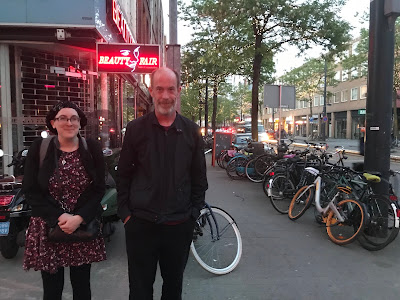 image: Sara Luterman, a white person with glasses and a knitted cap,  and Damian Milton, a white man with a salt-and-pepper beard, on a Rotterdam street littered with bicycles