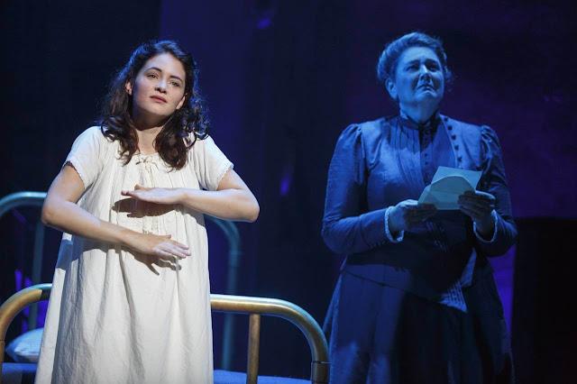 Sandra Mae Frank signando en la obra de teatro Spring Awakening con un camisón. A su lado, una mujer mayor con expresión triste y una carta en la mano
