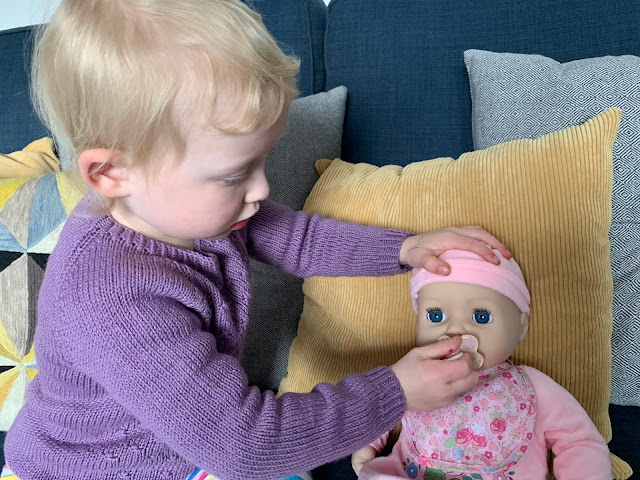 A toddler putting in the dummy on the interactive Baby Annabell doll