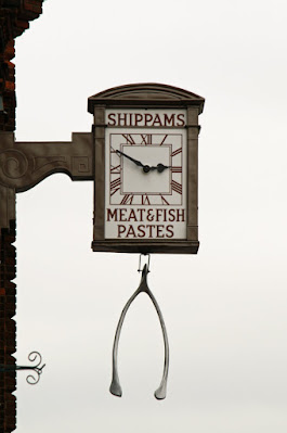 Photograph of a clock extending from a building facade on a scrolled bracket. The clock has a rectangular face with the word 'Shippams' above the dial, 'Meat & fish pastes' below. A large metal wishbone hangs beneath it.