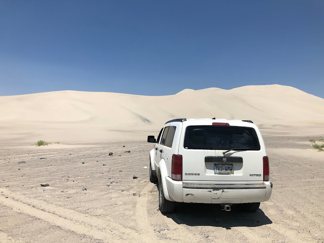 white SUV in front of large sand dune