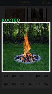 На поляне в яме горит костер и пламя поднимается в верх