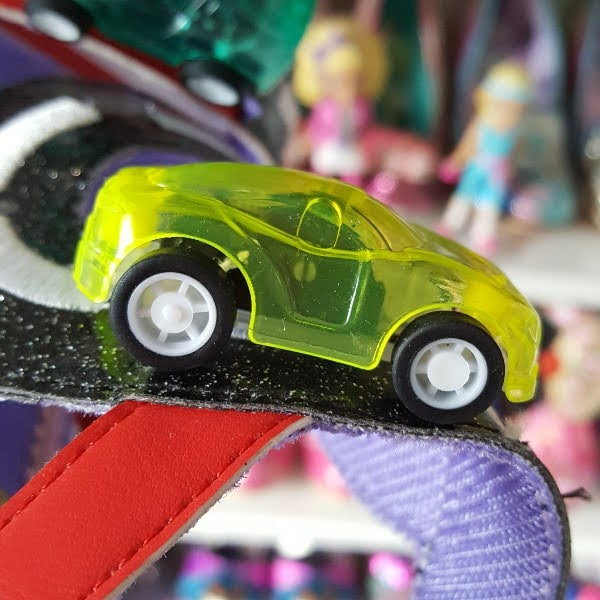 close up of racing car toy on strap of shoe