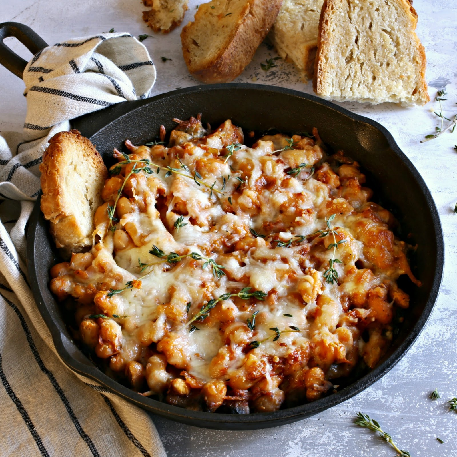 Recipe for white beans cooked in tomato and chicken stock, then baked with Parmesan and mozzarella cheese.