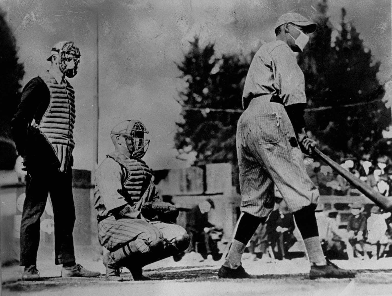Jogadores de beisebol não identificados, um rebatendo e outro pegando, além de um árbitro atrás do prato, usam máscaras contra a gripe.  1918