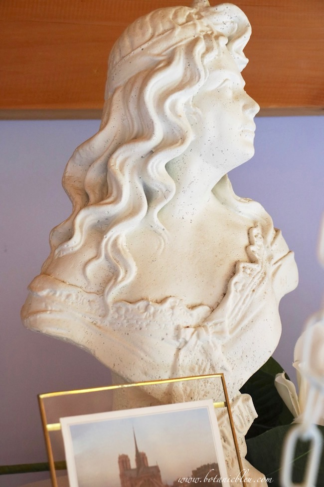 Elegant concrete bust of a girl is painted in white paint as part of the summer French Country swing loft.