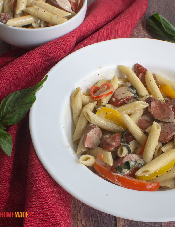 A white bowl with pasta and sausages and bell peppers