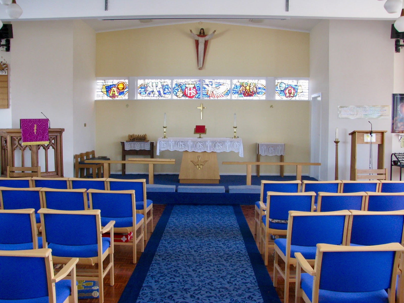 Image taken from left (entrance doors). Blue fabric wooden chairs lectern to left with organ and piano to left, alter to right of image.