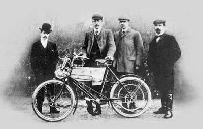 Group of men standing with 1901 Royal Enfield motorcycle.
