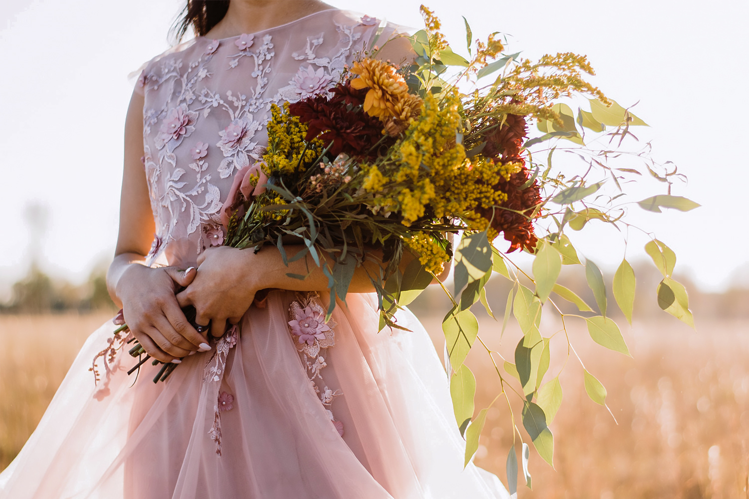 bride in the field holding wedding bouquet