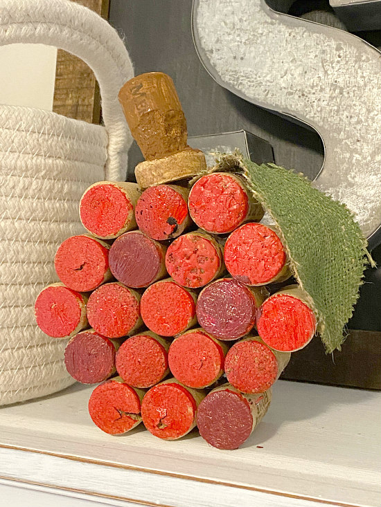red painted wine cork pumpkin on shelf with basket