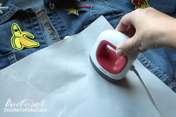 Step 3: Iron-on the Patches Heat up the Cricut EasyPress Mini to the highest setting. Glue back patches are so easy to press on a jacket, but the embroidery strings can burn if not careful, so using a cover sheet or teflon is super helpful.   Place the cover sheet over the patch and press the EasyPress down on it firmly. It takes a minute or so to heat up the glue backing and begin to adhere it to the jacket.  Move the EasyPress to all areas of the patch, especially the edges.