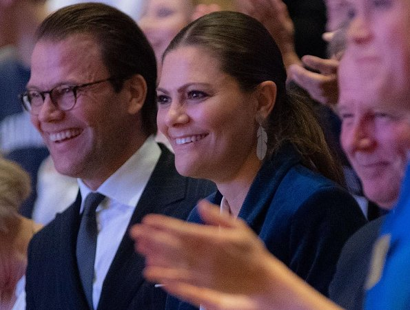 Crown Princess Victoria wore Yves Saint Laurent suede pumps, and she wore Kreuger Jewellery summer feather earrings at Karolinska Institute