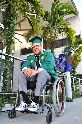 A man in a manual wheelchair is posing in front of a few palm trees. He wears a green graduation cap and gown. Smiling into the camera, he leans forward, folding his hands and wresting his wrists on his knees.