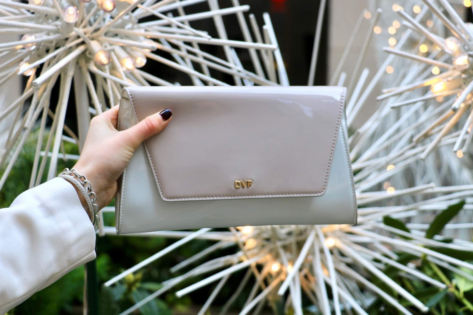 Nyc fashion blogger Kathleen Harper holding a Diane von Furstenberg white patent leather clutch.