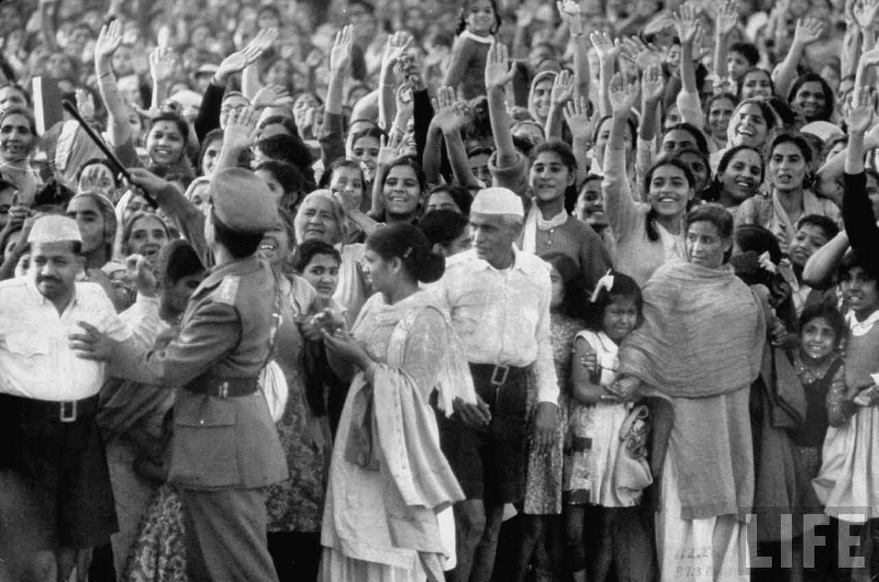 Multitud saludando a la reina Isabel durante su visita a la India.