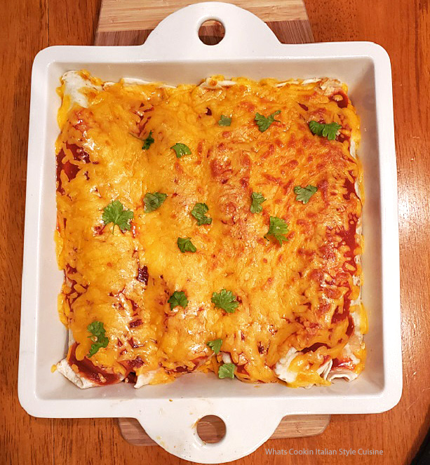 homemade baked enchiladas with sauce filled with corn, beef, rice and topped with cheese