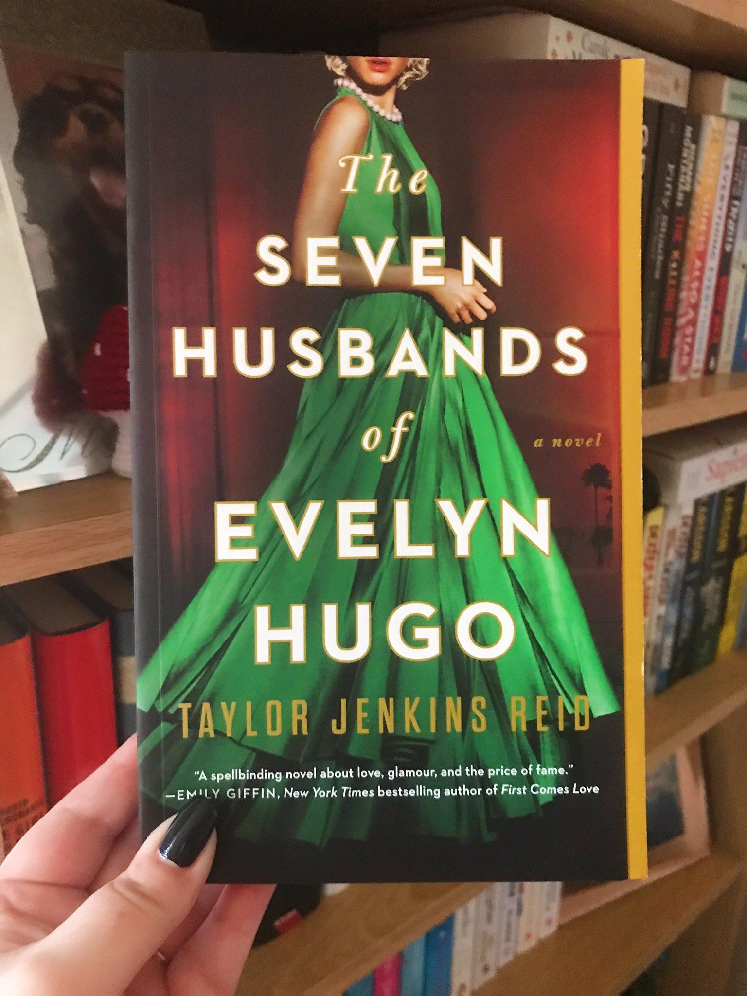 The Seven Husbands of Evelyn Hugo by Taylor Jenkins Reid held up in front of bookshelf