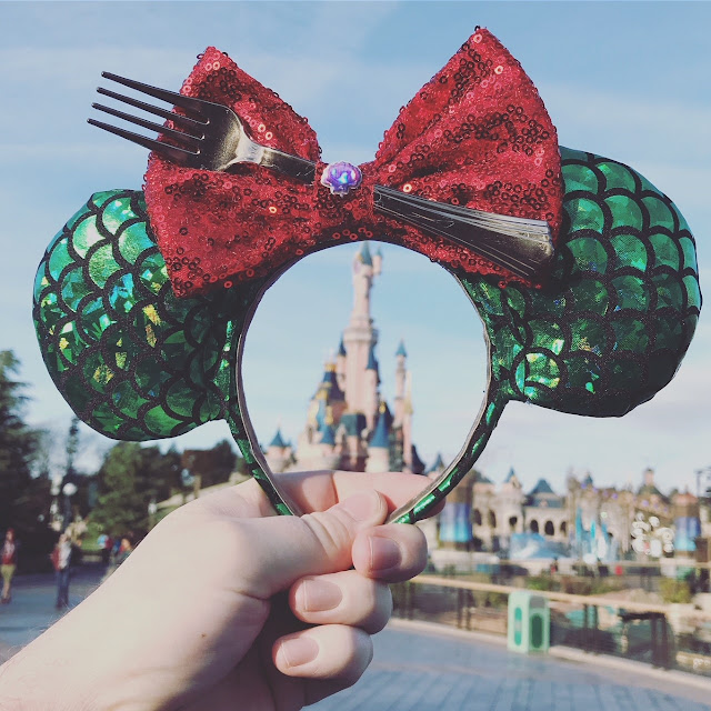 Pair of Ariel themed Mickey style ears held up in front of Sleeping Beauty's castle