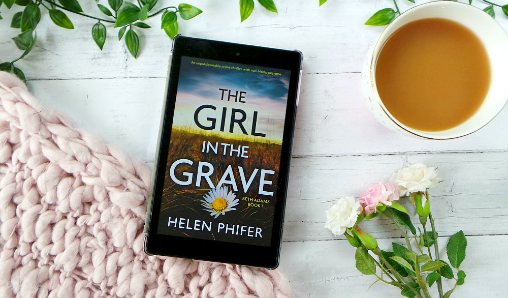 Kindle fire is on a table with some leaves, a pink chunky knit blanket and a cup of tea. The kindle shows the cover of the Girl in The grave. The cover shows a cloudy sky over a field with a solitary daisy