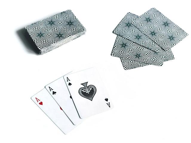 na zdjęciu widać stos kart dobierania, obok leżą cztery zakryte karty jednego z graczy oraz trzy odkryte asy osoby, ktróa wywołała kuku