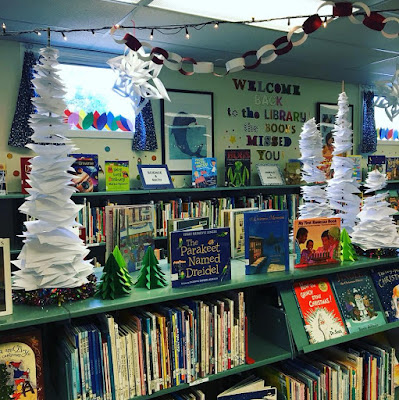 View of bookshelves and counters in library. White holiday lights are strung across ceiling, and pieces of paper are arranged on tall spindles, graded from larger sheets at base, to smaller at-top to suggest snow-covered trees. Winter holiday themed books are displayed on counter-top.