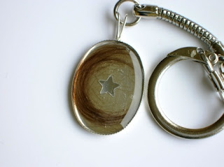 Silver keychain containing a lock of hair and star