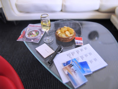 Modern one-twelfth scale miniature noguchi coffee table with a selection of postcards, a glass of wine and a travel magazine on it.