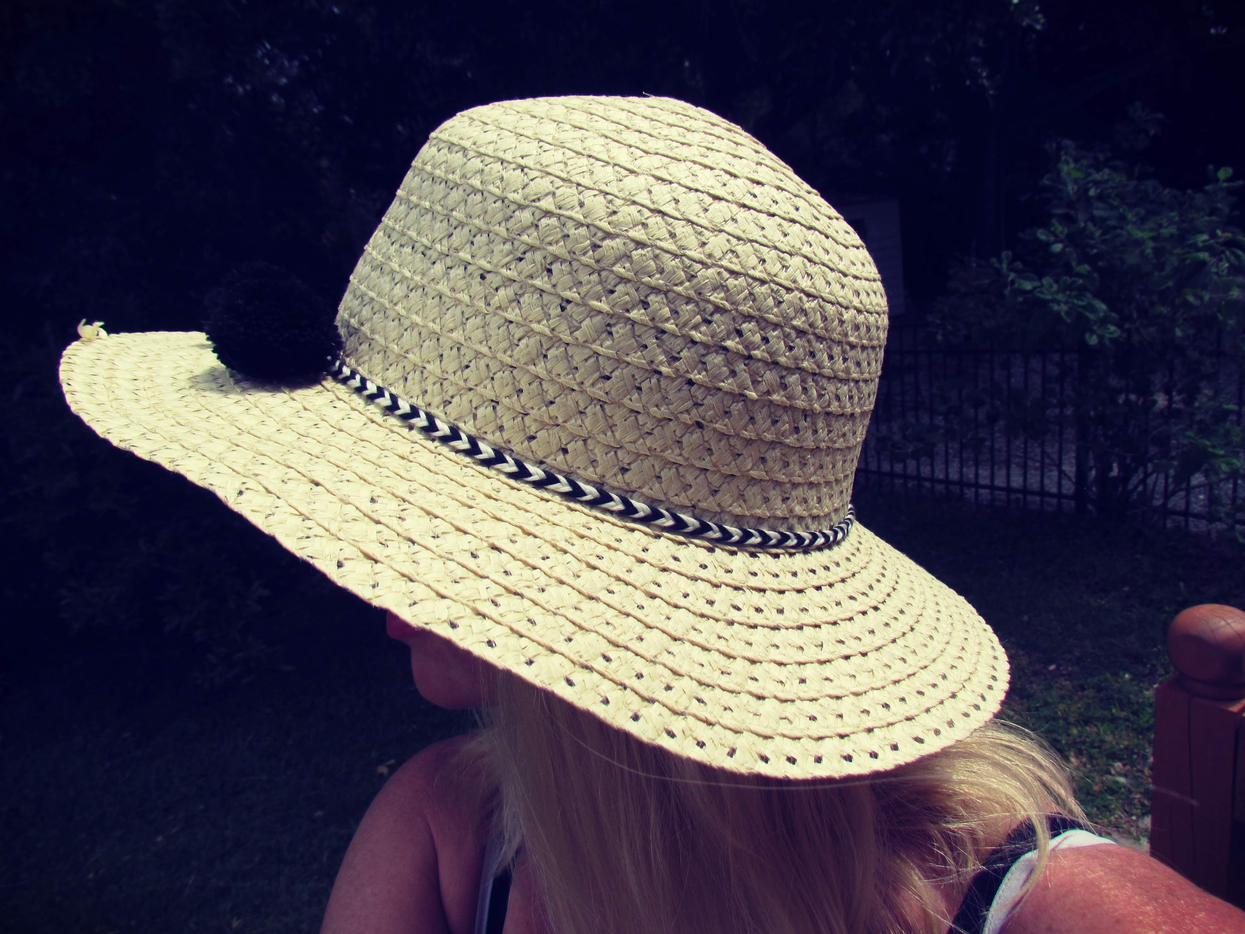 A woman in dark green grass with a cute sun hat on disguising her face