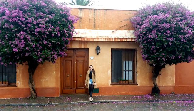 Menina em frente a uma casa marrom com árvores com flores roxas
