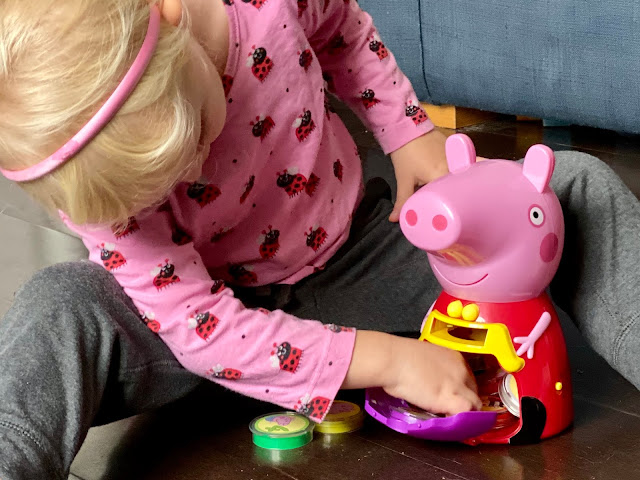 A 3 year old reaching into Peppa Pigs tummy to get the coins from her purse which is open on her front