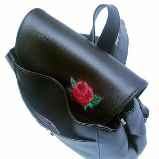 Detalle del bolsillo frontal en cartera mochial con aplique bordado