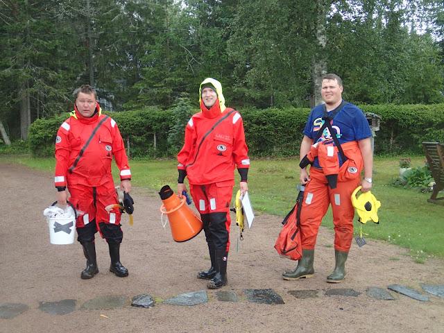 Kolme henkeä pelastautumispuvuissa ämpärien kanssa