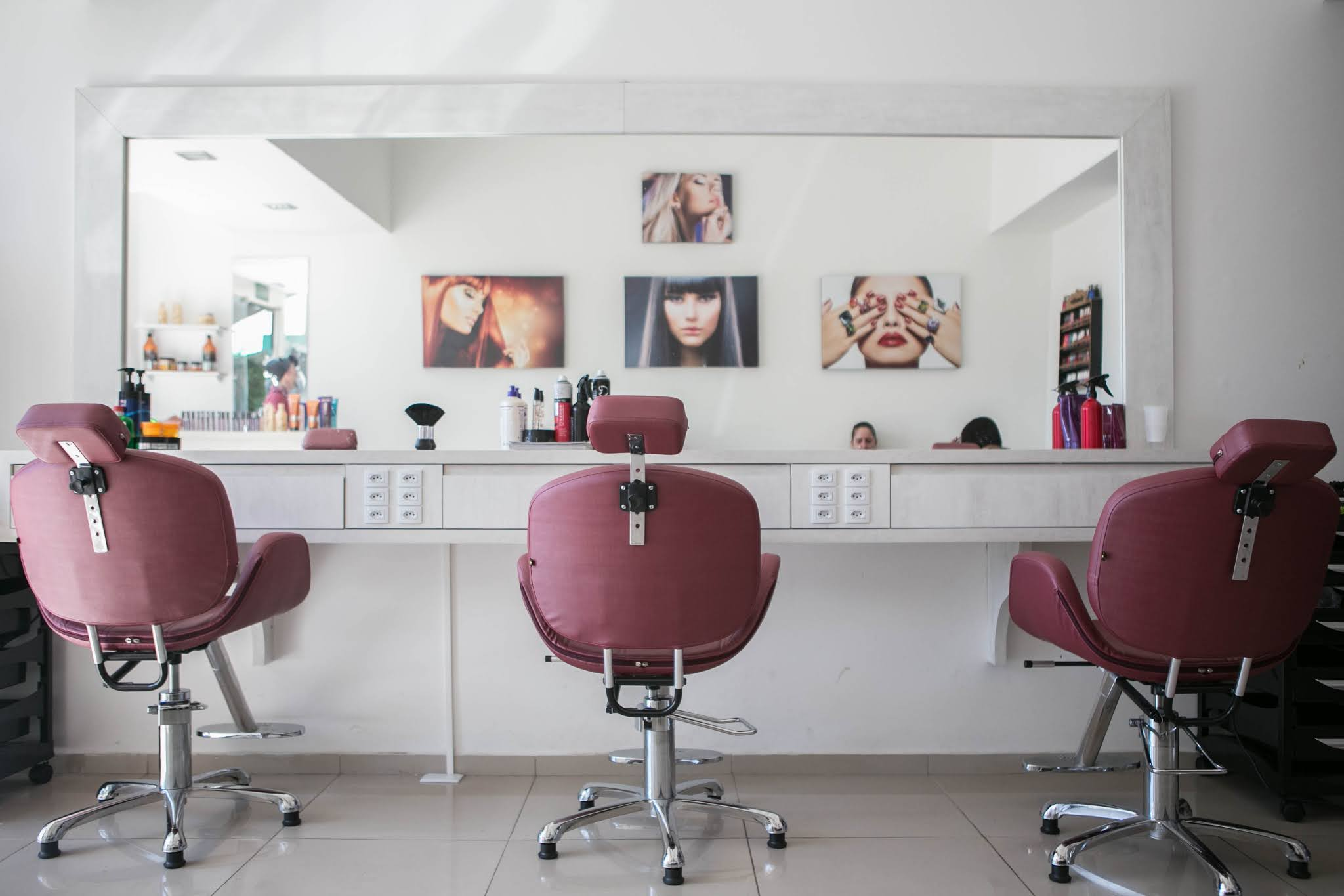 three hairdresser chairs alongside mirrors