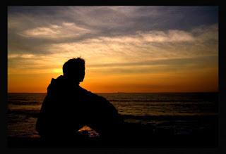 Paisagem do crepúsculo, homem solitário sentado na areia da praia contempla o horizonte.