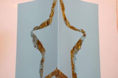 Postal com contorno de estrela feito de glitter, em cartolina azul clara