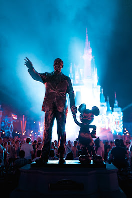 Statue of Walt Disney and Mickey Mouse with fireworks in background