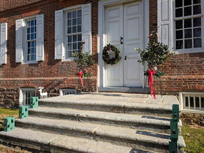18th century brick mansion with stone steps in front, decorated with Christmas greenery
