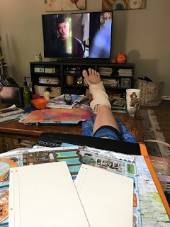 photo of my leg, ankle wrapped on table, crafting supplies on my lap.
