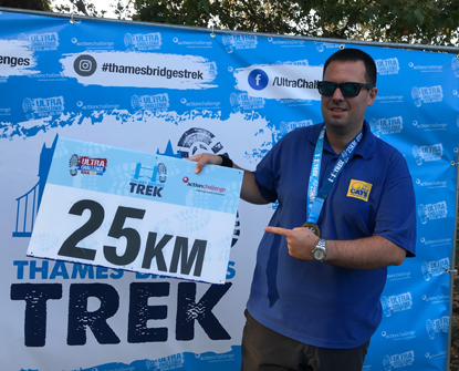 man holding 25KM sign at race finish line