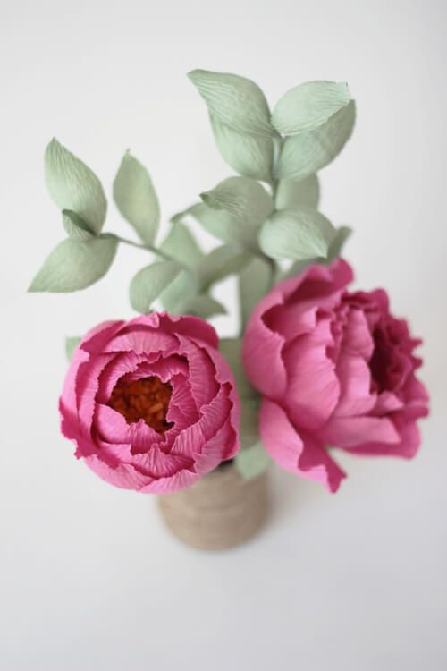 pair of deep pink crepe paper peonies with green foliage in vase