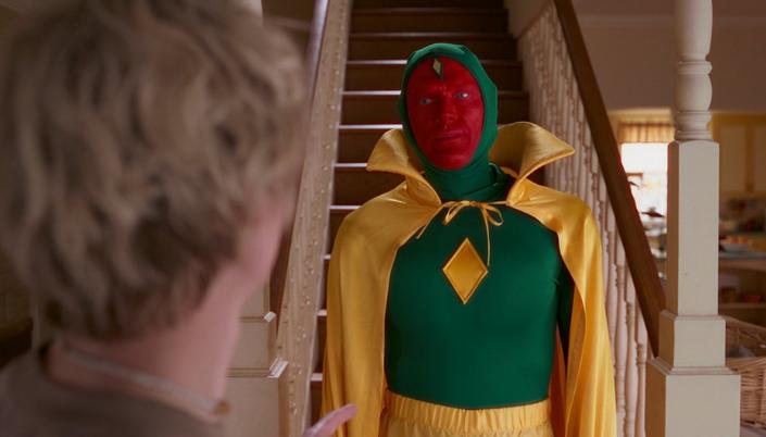 Imagem: Visão fantasiado como o seu uniforme das HQs, com uma roupa que cobre o seu corpo todo em verde-vivo, uma capa amarela e um losango amarelo no seu peito e a nuca de Pietro, com cabelos brancos, virado para ele.